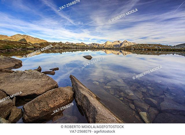 Peaks are reflected in Lake Bergsee at dawn Chiavenna Valley Spluga Valley Switzerland Europe