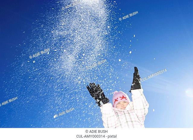 Young girl throwing snow in the air