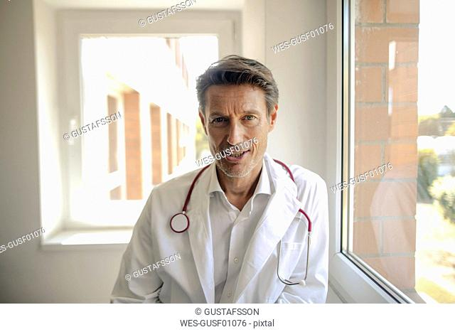 Doctor standing in hospital with stethoscope around neck, portrait