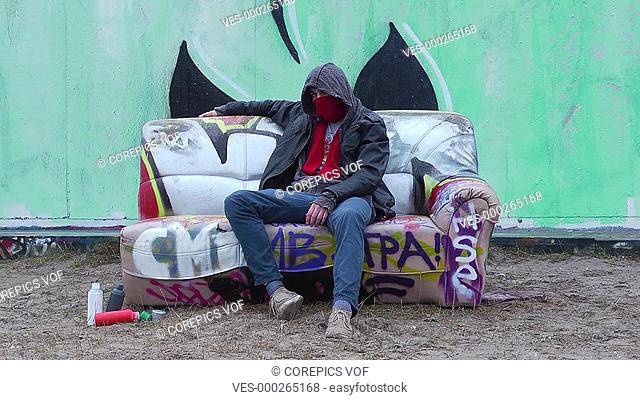 Graffiti Artist, sitting on a couch, relaxing after finishing his artwork, with a few spray cans on the sand next to him