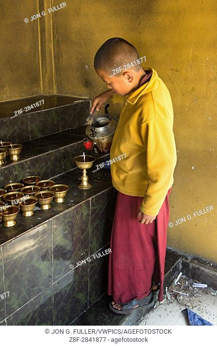 A young Buddhist monk prepares butter lamps at the Punakha Stupa in Punakha, Bhutan