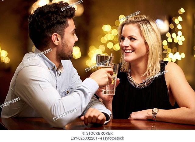 Couple Enjoying Evening Drinks In Bar