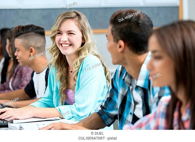Row of teenage high school students smiling in computer class