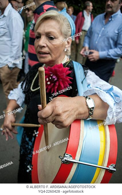 Women dressed in traditional costume, drumming during the procession in Lledías, Llanes, Asturias