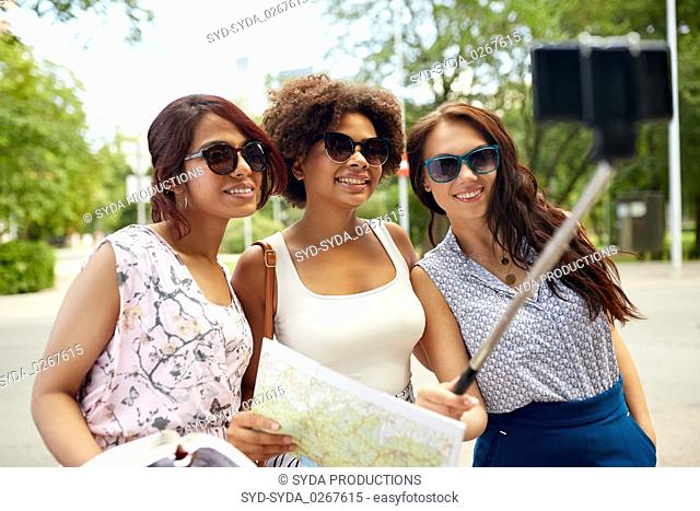 women with city guide and map taking selfie