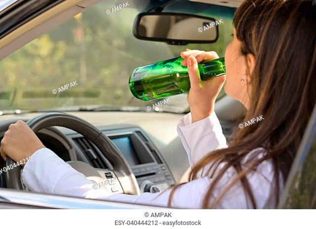 Woman drinking alcohol and driving raising the bottle to her lips to take a swig as she steers the car, view through the side window