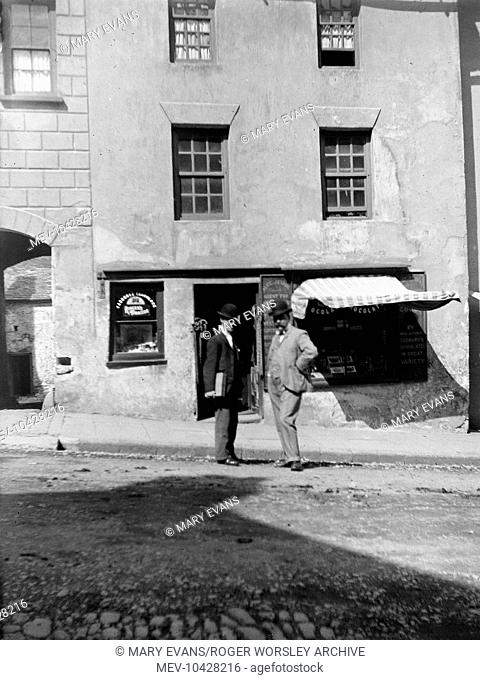 Two men standing outside a confectionery and tobacco shop in the High Street, Haverfordwest, Pembrokeshire, Dyfed, South Wales look straight at the camera
