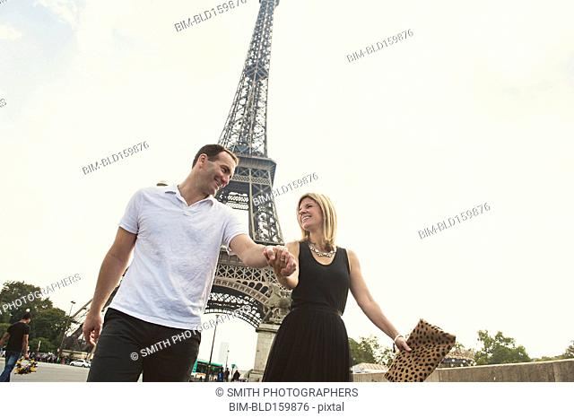 Caucasian couple walking near Eiffel Tower, Paris, Ile-de-France, France