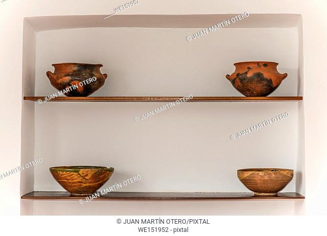 four clay pots placed on two wooden shelves. behind a white wall