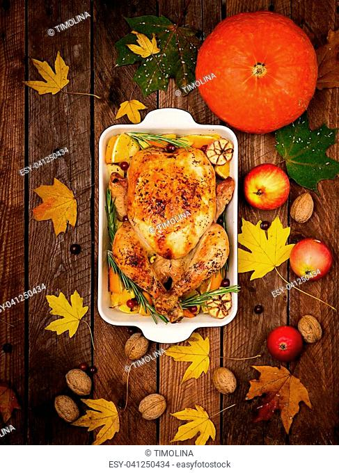 Roasted turkey garnished with cranberries on a rustic style table decorated with pumpkins, orange, apples and autumn leaf. Thanksgiving Day. Flat lay