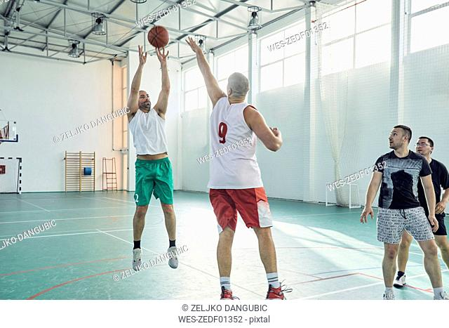 Men playing basketball, indoor