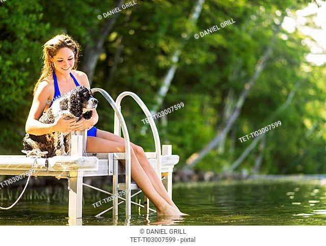 Young woman with dog sitting on jetty over lake