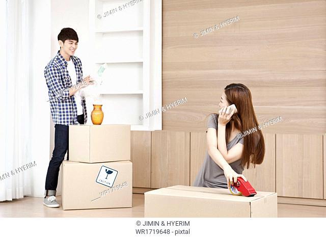 A woman closing a moving box