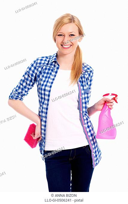 Blonde female cleaner holding a sponge and spray, Debica, Poland