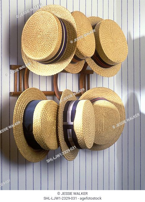 HAT COLLECTION DISPLAY: Mens vintage straw hats on a wall rack, striped wallpaper