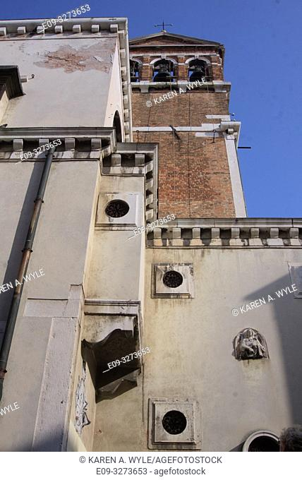 architectural contrast, brick church tower behind very different building with odd round windows set in squares and one wall sculpture showing, Venice, Italy