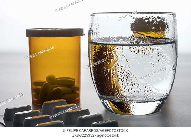 Water glass frozen along with pills, conceptual image