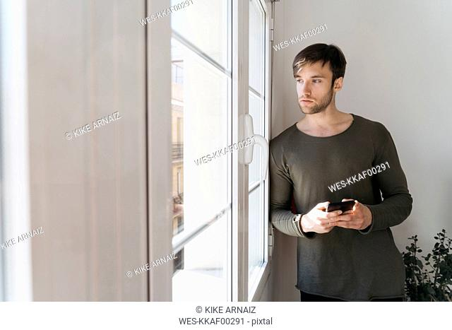 Young man with smartphone looking through window