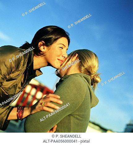 Teenage girls kissing cheeks