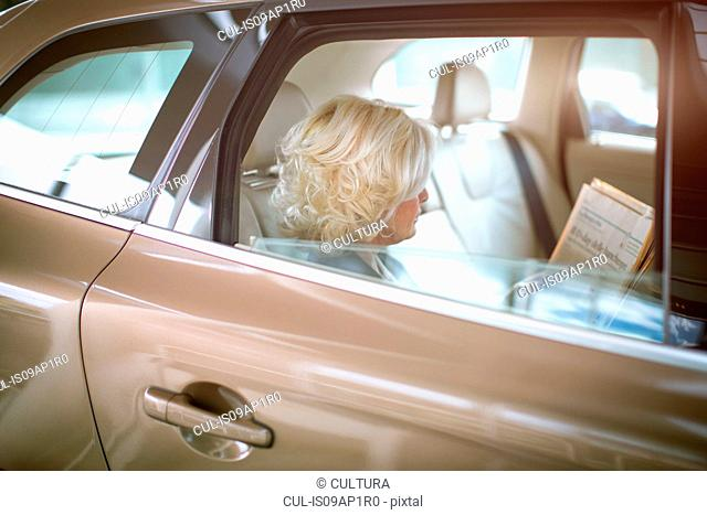 Mature businesswoman sitting in car, looking through documents