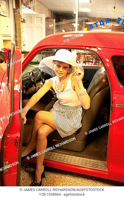 Female model in wide-brimmed white hat by antique red automobile