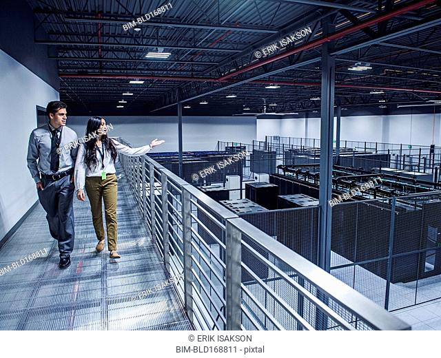 Businesswoman showing colleague server room from balcony