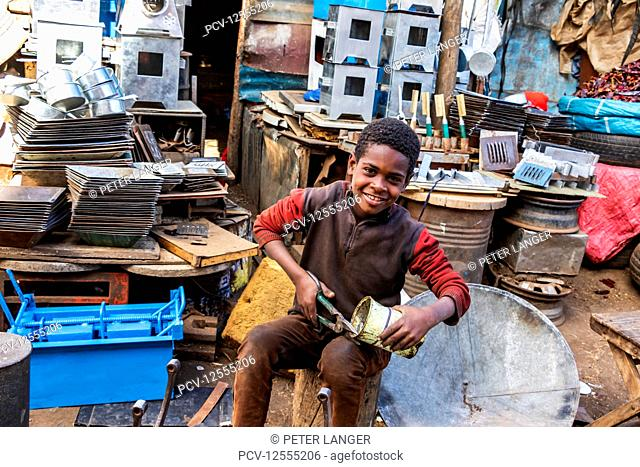 Eritrean boy cutting a can at the Medeber Market, where artisans recycle old tyres and tins to make new artifacts; Asmara, Central Region, Eritrea