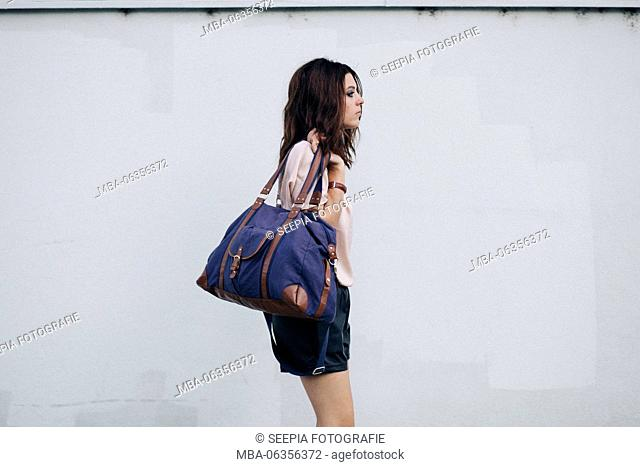 Young attractive brunette woman with blue pouch in front of white wall