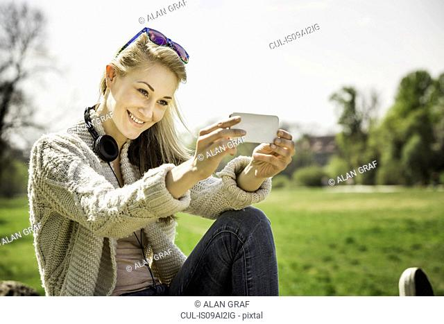 Young woman posing for self portrait in park