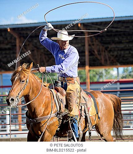 Older Caucasian cowboy throwing lasso at rodeo