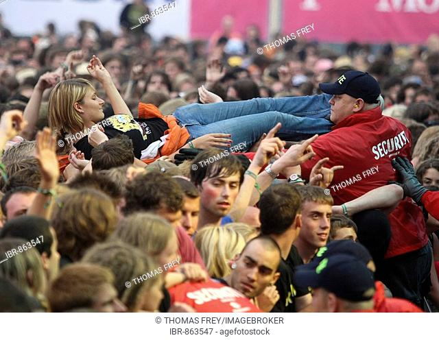 Member of the security force taking care of body surfers in front of the main stage at the Rock am Ring 2008 Music Festival, 06.06