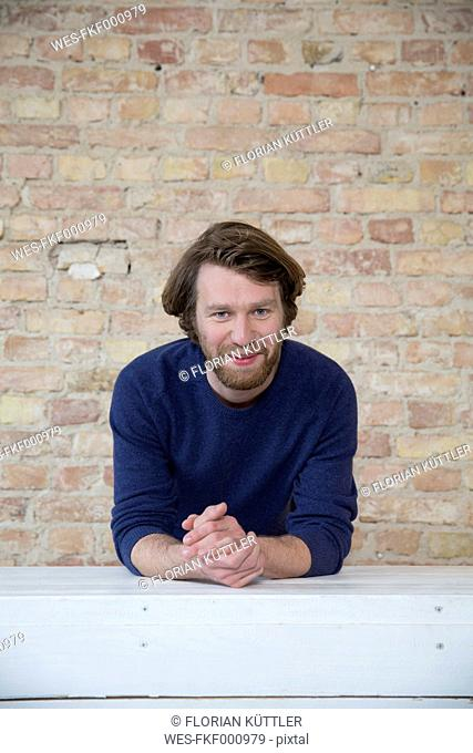 Portrait of smiling man in front of brick wall