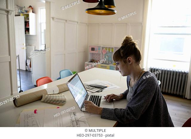 Interior designer working at laptop at dining room table