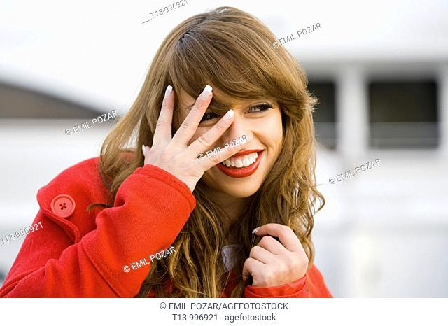 Peeking and smiling through fingers pretty woman portrait