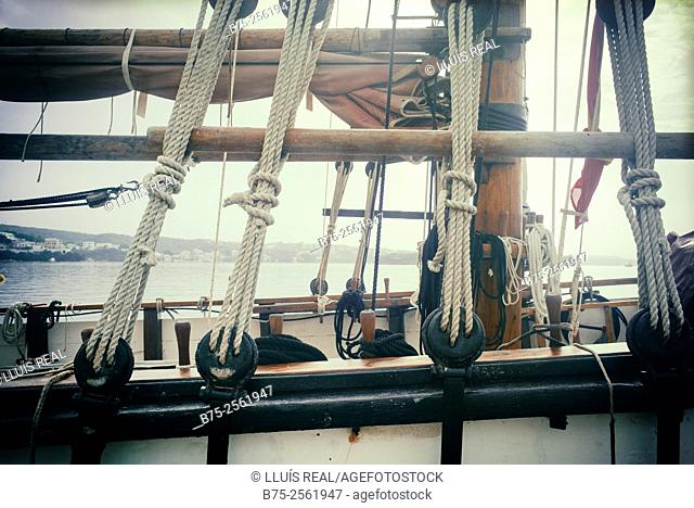 Close-up of the cover of a vintage sailing boat with mast, rigging, ropes and pulleys in Mahon harbor. Maó, Menorca, Biosphere Reserve, Balearic Islands, Spain