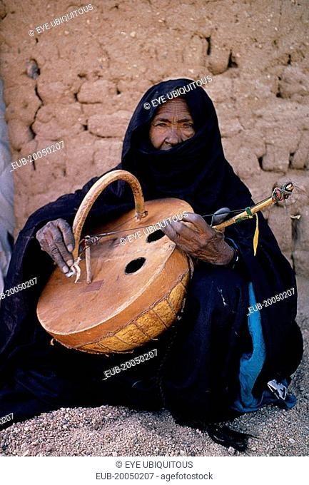 Tuareg woman playing an Imzad. Traditional instrument consisting of a goatskin covered gourd or wooden resonator played with a curved bow and horsehair string