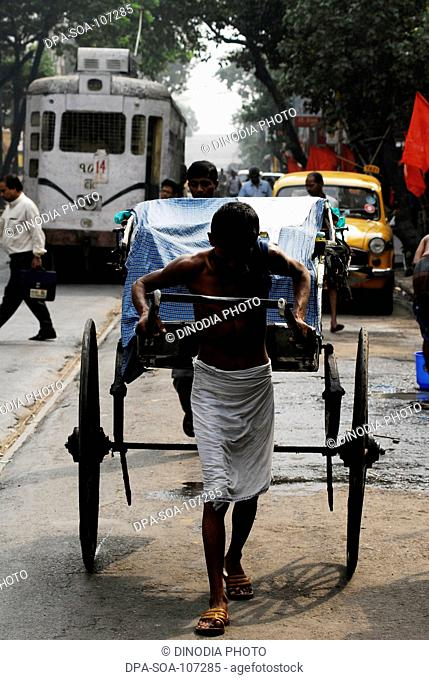 Hand Rickshaw puller pulling empty Vehicle ; Kolkata ; West Bengal ; India
