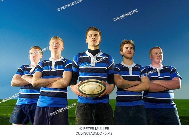 Portrait of rugby team, one man holding ball
