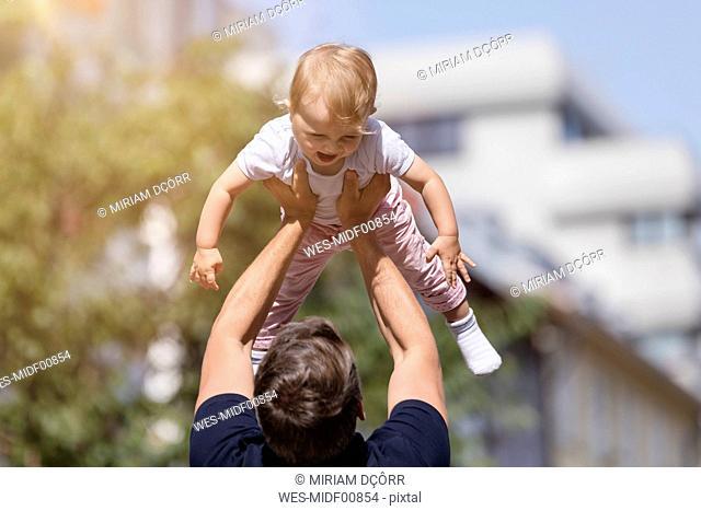Father holding little daughter aloft