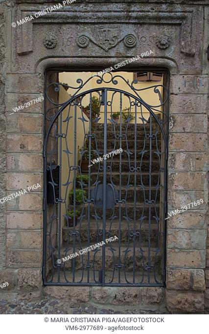 An old metal wrought iron gate in the small village of Bortigali, Sardinia, Italy. The stoneworks dates back to 1605