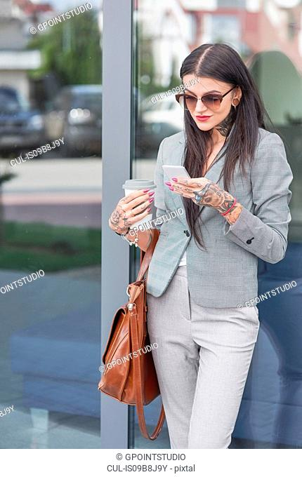 Businesswoman outdoors, holding coffee cup, using smartphone, tattoos on hands