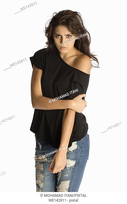 Serious young woman wearing ripped jeans staring