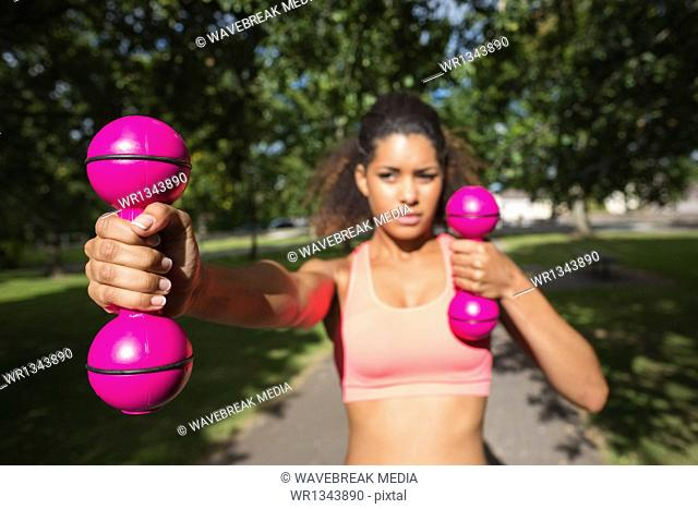 Fit young woman exercising with dumbbells in park
