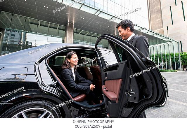 Businessman opening car door for businesswoman