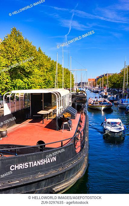Tourist sightseeing boat passing houseboat on Christianshavn Canal, Copenhagen, Denmark, Scandinavia
