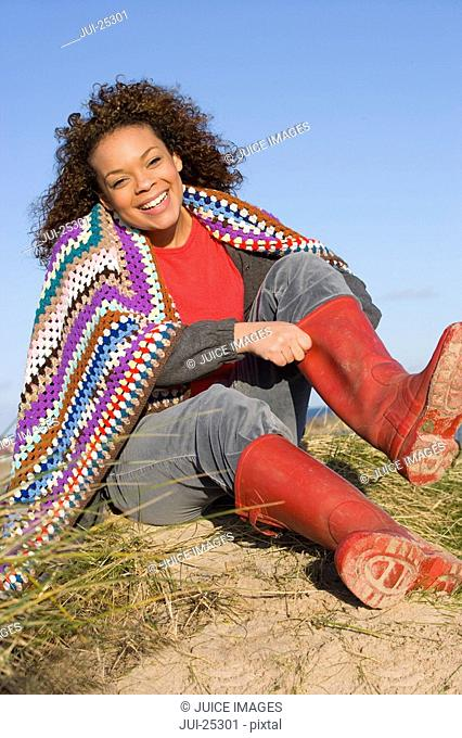 Smiling woman wrapped in blanket putting on rubber boots