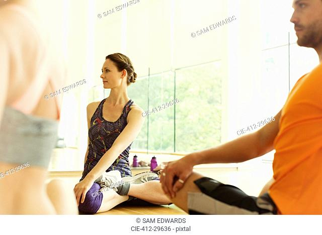 Fitness instructor leading class in twisting stretch
