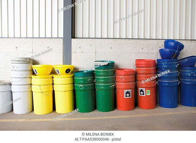 Multicolored garbage cans and recycling bins stacked along wall