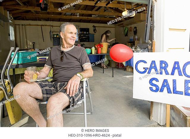 Smiling man sitting next to garage sale sign