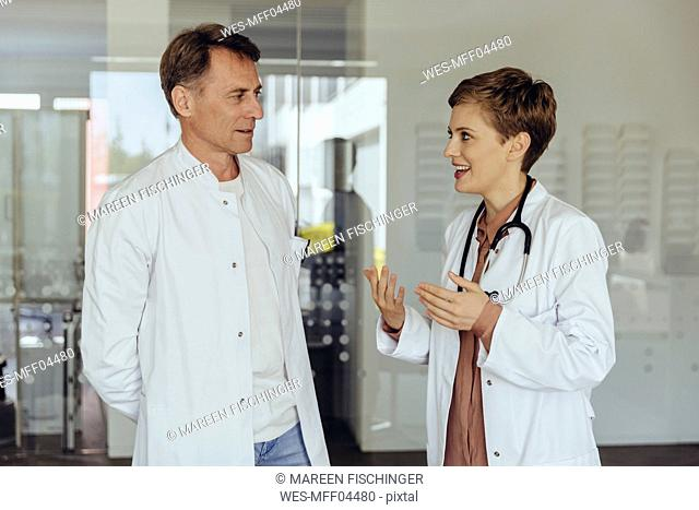 Two confident doctors standing in practice, discussing